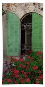 Green Windows And Red Geranium Flowers Bath Towel by Yair Karelic