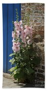 Pink Hollyhocks Growing From A Crack In The Pavement Hand Towel