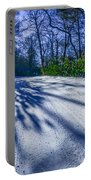 Snow Covered Road Leads Through The Wooded Forest Portable Battery Charger