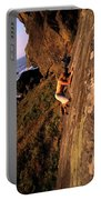 A Man Is Bouldering Near The Ocean Portable Battery Charger