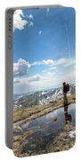 A Backpacker Stands Atop A Mountain Portable Battery Charger