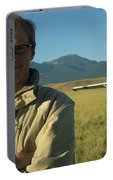 A Man Stands In A Field Next Portable Battery Charger