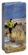A Man Trail Runs On A Winter Day Portable Battery Charger