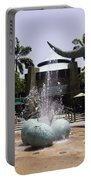 A Water Fountain With Dinosaur Eggs And Dinsosaurs In Universal Studios Portable Battery Charger