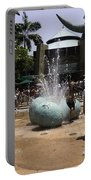 A Water Fountain With Dinosaur Eggs In Universal Studios Singapore Portable Battery Charger