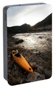 A Whitewater Kayak Rests On The Shore Portable Battery Charger