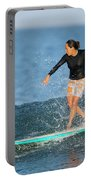 A Woman Rides A Wave On A Longboard Portable Battery Charger