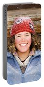 A Woman Stands Against A Log Cabin Portable Battery Charger