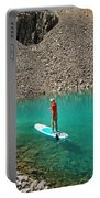 A Young Male Paddleboarding On A Small Portable Battery Charger