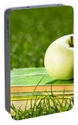 Apple On Pile Of Books On Grass Portable Battery Charger