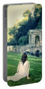 Lady Sitting On A Hill Above A Lake Portable Battery Charger