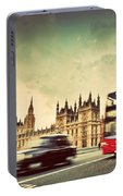 London The Uk Red Bus Taxi Cab In Motion And Big Ben Portable Battery Charger
