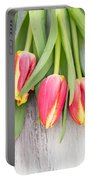 Many Spring Tulip Flowers On White Wood Table Portable Battery Charger
