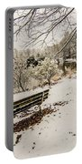 Park Bench In The Snow Covered Park Overlooking Lake Portable Battery Charger