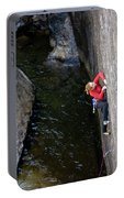 Woman Climbing Above A River Portable Battery Charger