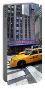 Yellow Cabs Pass In Front Of Radio City Music Hall Portable Battery Charger