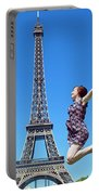 Young Woman Jumping Against Eiffel Tower Portable Battery Charger