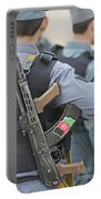 An Ak-47 Rests On The Sling Of An Portable Battery Charger