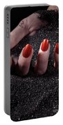 Woman Hand With Red Nails On Black Sand Portable Battery Charger