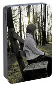 Girl Sitting On A Wooden Bench In The Forest Against The Light Portable Battery Charger