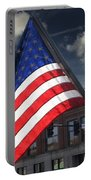 American Flag Flowing In Urban Landscape Portable Battery Charger