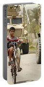 An Iraqi Boy Rides His Bike Past A U.s Portable Battery Charger by Stocktrek Images