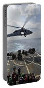 An Mh-60r Sea Hawk Transfers Supplies Portable Battery Charger