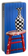 Blach And White Vase On Stool Against Blue Wall Portable Battery Charger