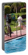 Cycle Near A Swimming Pool And Greenery Portable Battery Charger