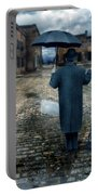 Man In Vintage Clothing With Umbrella On Rainy Brick Street Portable Battery Charger