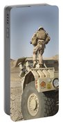 Soldier Climbs A Damaged Husky Tactical Portable Battery Charger by Stocktrek Images