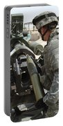U.s. Army Soldier Loads A 105mm Portable Battery Charger