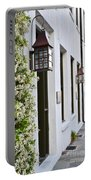 Colonial Home Exterior With Vertical Plants And Old Lanterns Displayed On The Side Of Home Portable Battery Charger