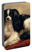 A King Charles Spaniel Seated On A Red Cushion Portable Battery Charger
