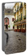 Cobblestone Argote De Molina Street With Cafe Ending At The Nort Portable Battery Charger