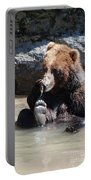 Grizzly Bear Licking His Paw While Seated In A Muddy River Portable Battery Charger
