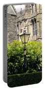 Lamppost In Front Of Green Bushes And Old Walls. Portable Battery Charger