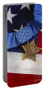 The Medal Of Honor Rests On A Flag Portable Battery Charger