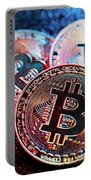 Three Bitcoin Coins In A Colorful Lighting. Portable Battery Charger