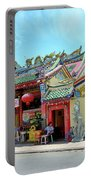 Woman Sits Outside Chinese Temple With Urn And Deity Statues Pattani Thailand Portable Battery Charger
