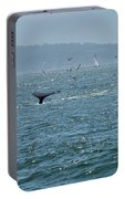 A Whale's Tail Above Water With Sail Boat In The Background Portable Battery Charger