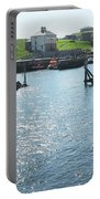 sunlight glistening on water at Eyemouth harbour Portable Battery Charger