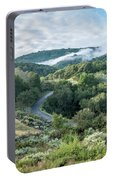 View Of Curved Road Through Dense Forest Area With Low Clouds Ov Portable Battery Charger