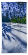 Snow Covered Road Leads Through The Wooded Forest Beach Towel