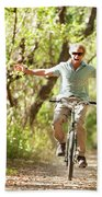 A Man Rides A Bicycle Beach Towel