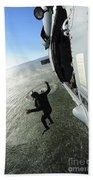 A Naval Air Crewman Jumps From An Beach Towel