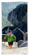 A Woman Hiking High In The Mountains Beach Towel