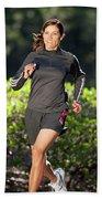 An Athletic Woman Trail Running Beach Towel