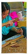 Child Watches As Mom Works In Teak Wood Carving Shop In Kanchanaburi-thailand Beach Towel
