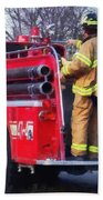 Fireman On Back Of Fire Truck Beach Towel